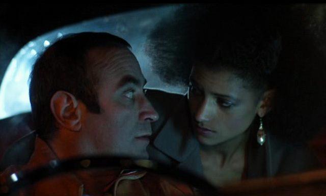 Nahaufnahme von George am Steuer und Simone, die sich zu ihm von der Rückbank aus nach vorne beugt.