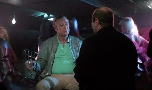Michael Caine als Gangster Mortwell, der mit einem Sektglas in einem Lederstuhl sitzt, George zugewandt.