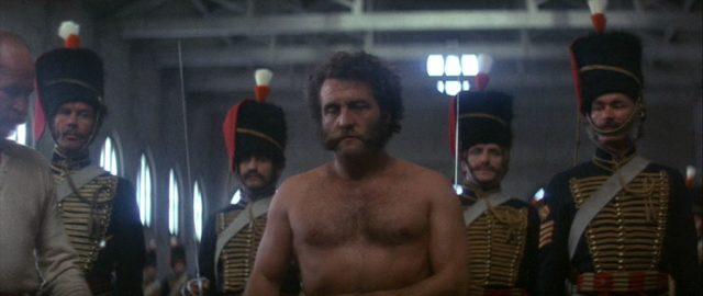 Der zu bestrafende Soldat mit entblößtem Oberkörper in Begleitung mehrerer Soldaten kurz vor Ausführung der Strafaktion.