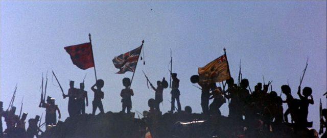 Die Silhouette Fahnen schwingender Soldaten der britischen Armee auf einem Hügel.