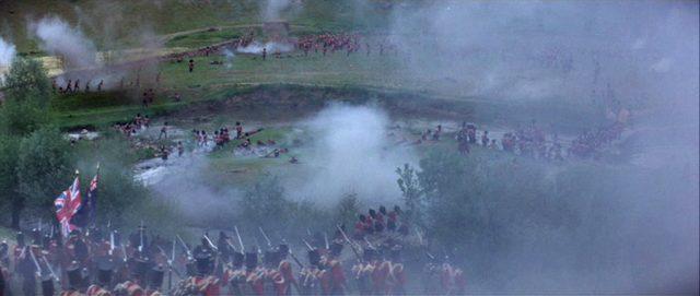 Blick auf britische Truppen auf ihrem Weg in die Schlacht, zwischen ihnen der Rauch detonierter Geschosse.