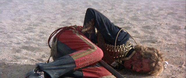 Ein britischer Soldat mit schmerzverzerrtem Gesicht liegt auf dem Schlachtfeld und fasst sich an den Unterleib, in welchem eine Lanze steckt.