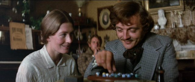 Nahaufnahme von Vanessa Redgrave und David Hemmings, deren Charaktere sich mit fröhlichen Gesichtern beim Murmelspiel die Zeit vertreiben.