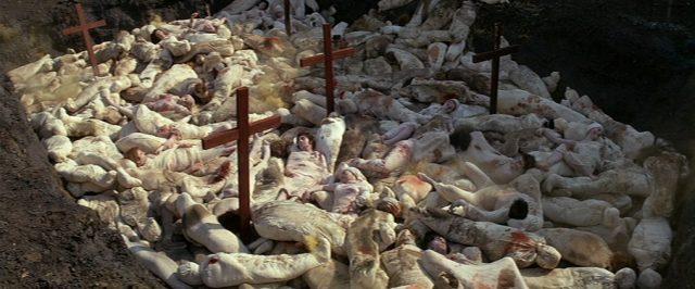 Blick in eine Grube voller Pestleichen, zwischen denen Kreuze herausragen.