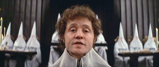 Nahaufnahme von Dudley Sutton als Grandiers Gegenspieler bei der Gerichtsverhandlung.