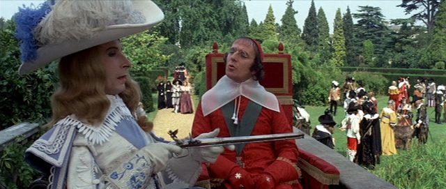 König Ludwig XIII., gespielt von Graham Armitage, in exaltiertem Outfit und im Beisein des in Robe gekleideten Kardinal Richelieu, gespielt von Christopher Logue.