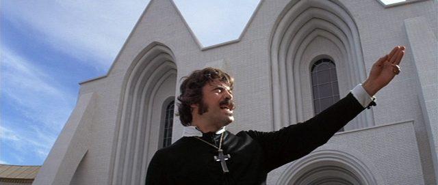 Grandier mit ausgestrecktem Arm in charismatischer Pose bei einer Rede unter freiem Himmel vor dem weißen Kirchengebäude.