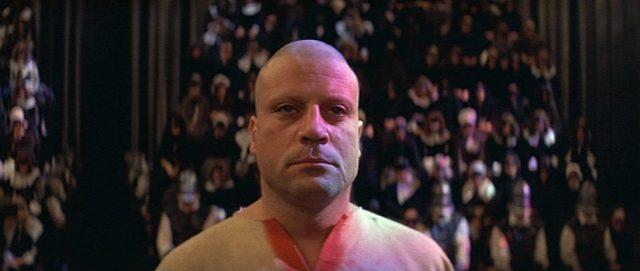 Nahaufnahme des kahlrasierten, in ein schlichtes Hemd gekleideten Grandier mit ernsthafter Mimik im Angesicht des Tribunals, im Hintergrund die Zuschauer, die dem Schauprozess beiwohnen., Copyright: Warner Bros.