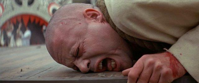 Nauaufnahme des mit schmerzverzerrtem Gesicht über Holzbohlen kriechenden Grandier.