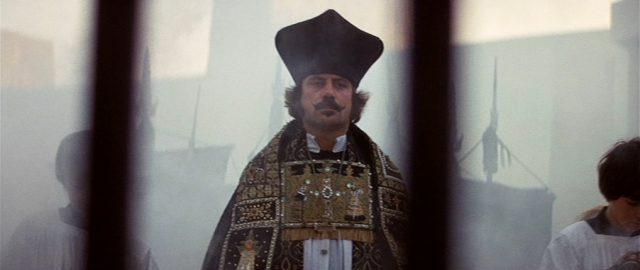 Blick durch Gitterstäbe auf den herannahenden Priester Grandier in feierlicher Robe (gespielt von Oliver Reed).