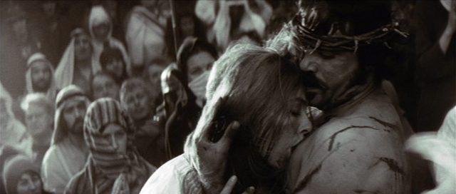 In einer in Schwarz-Weiß gezeigten Traumsequenz küsst Schwester Jeanne, gespielt von Vanessa Redgrave, die Wunden von Jesus, dargestellt von Oliver Reed., Copyright: Warner Bros.