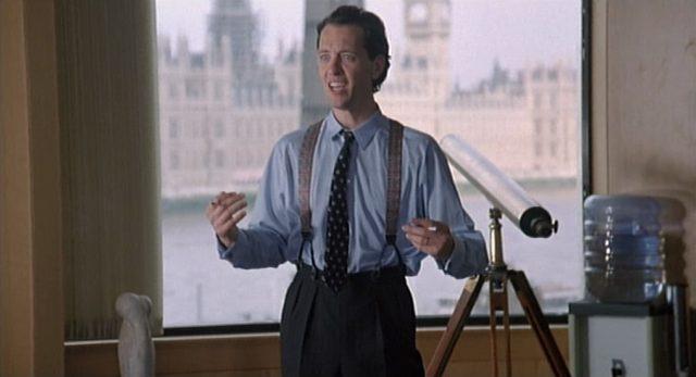 Richard E. Grant als Denis Dimbleby Bagley, der in Yuppie-Klamotten im Büro steht, im Hintergrund erkennt man die Themse, das Parlamentsgebäude und Big Ben.