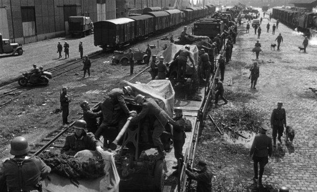 Deutsche Soldaten beim emsigen Verladen von Kriegsmaterial auf einen Zug an einem Güterbahnhof in Frankreich.