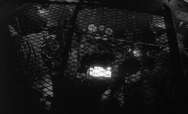 Blick durch ein Gitter in den dusteren Arbeitsbereich des Lokführers, die Ofenklappe ist geöffnet.