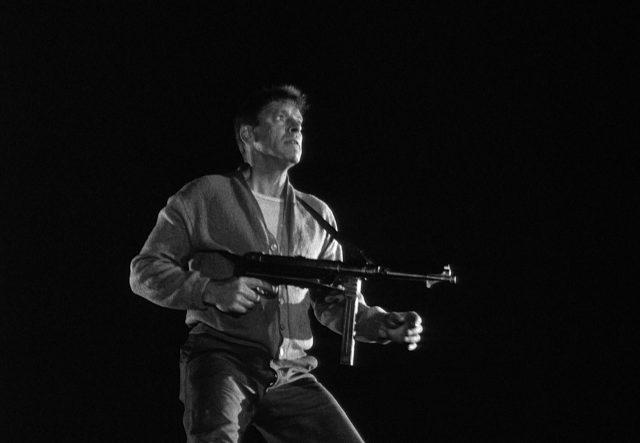 Burt Lancaster als Labiche vor völlig dunklem Hintergrund mit einer MP 40 bewaffnet.