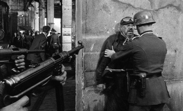 Michel Simon als französischer Lokführer Papa Boule, der hier von einem Wehrmachtssoldaten zur Exekution an eine Mauer gestellt wird, im Vordergrund sind zwei Maschinenpistolen vom Typ MP 40 zu sehen.
