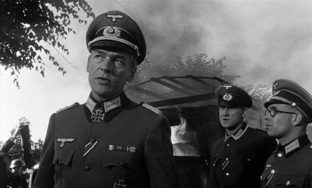 Oberst von Waldheim (gespielt von Paul Scofield) im Beisein zweier Soldaten.
