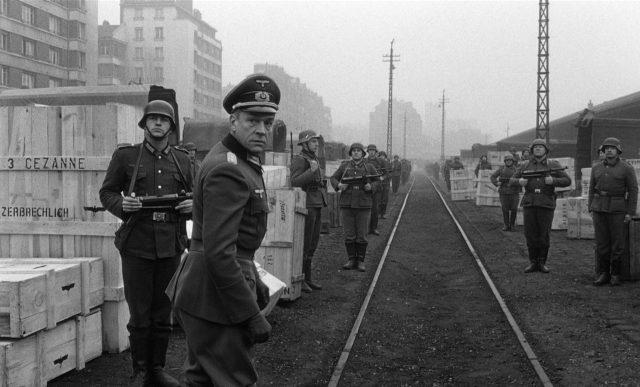 Neben den Gleisen stehen von deutschen Soldaten bewachte Holzkisten, Oberst von Waldheim (gespielt von Paul Scofield) dreht sich gerade in Richtung der Kamera um; im Hintergrund sind Gebäude einer Stadt zu erkennen.