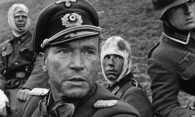 Nahaufnahme von Wolfgang Preiss als Major Herren, im Hintergrund sind drei ramponierte Wehrmachtssoldaten zu sehen.