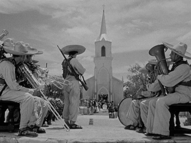 Ein Orchester der Rebellen, im Hintergrund eine Kirche mit Hochzeitsgesellschaft.