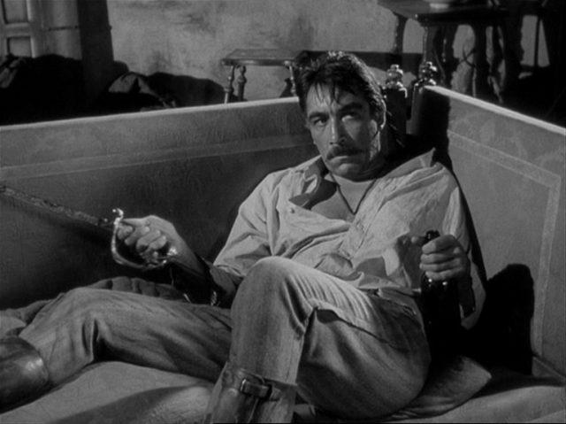 Anthony Quinn als Zapatas Bruder Eufemio, der mit Säbel und einer Flasche mit latent aggressivem Blick auf einem Sofa liegt.