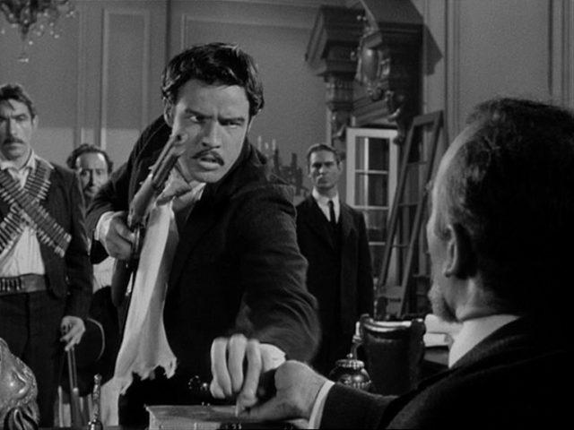 Zapata bedroht mit wütender Miene den neuen mexikanischen Staatspräsidenten an dessen Schreibtisch mit einem Gewehr.