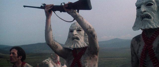 Nahaufnahme einer Gruppe Brutal Exterminators, von denen zwei mit Zardoz-Masken maskiert sind; einer von Letzteren hält mit beiden Händen ein Gewehr hoch.