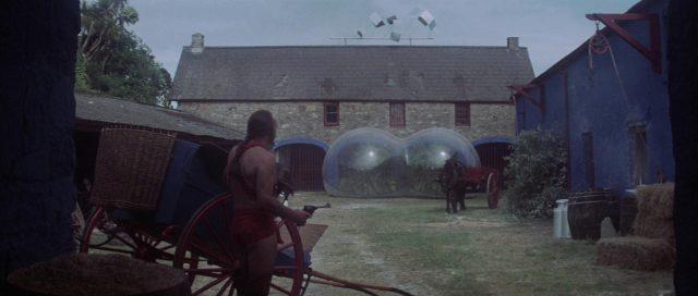 Im Vordergrund steht der von Sean Connery gespielte Exterminator, bewaffnet mit einem Revolver, und blickt auf den Innenhof des Vortex-Gehöfts der Eternals.