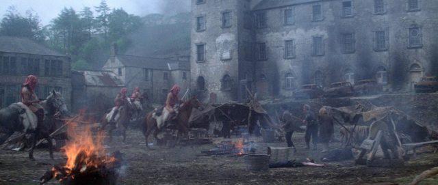 Eine Gruppe maskierter Exterminators reitet durch ein desolates Lager der Brutals, im Hintergrund sind marode Fahrzeuge und ein halb verfallenes Gebäude zu sehen, im Vordergrund lodert ein Lagerfeuer.