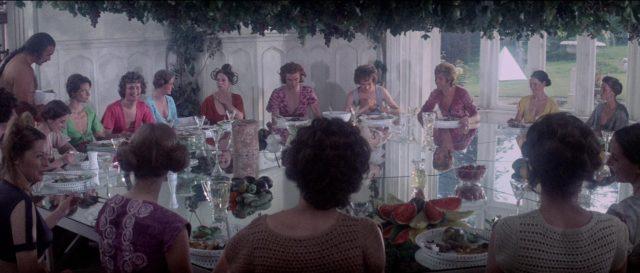 Die Eternals sitzen um eine Tafelrunde aus Spiegelglas herum und lassen sich von Zed bedienen.