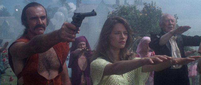 Zed steht mit ausgestrecktem Arm und Revolver neben Consuella, die beide Arme ausgestreckt hat.
