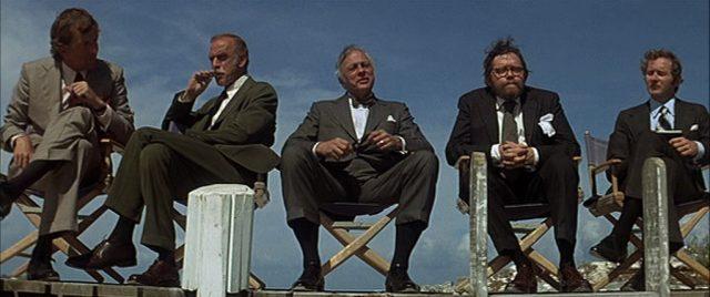 Ein Gremium dubioser Männer, die in Klappstühlen Platz genommen haben.