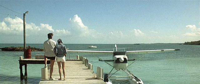 Ein kleines Flugzeug wassert an einem Steg, an dem die Terrells gen Horizont blicken.