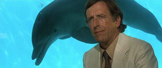 Nahaufnhame von Fritz Weaver als Stiftungschef, im Hintergrund schwimmt ein Delfin hinter einer Glaswand.