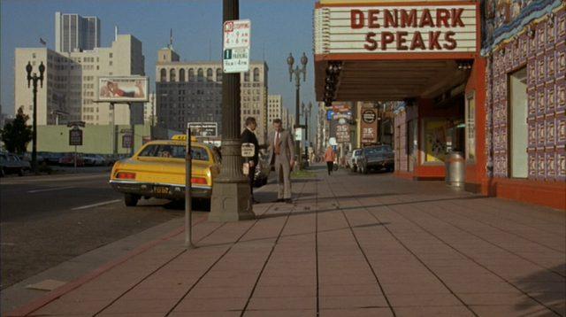Blick in eine Straße von Los Angeles, wo Harry Stoner und Phil Greene an einem Taxi stehen.