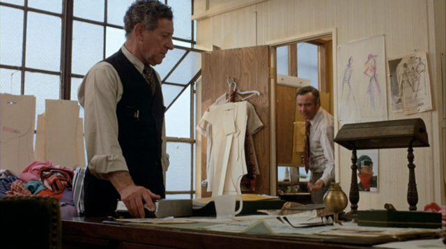 Phil Greene steht in der Fabrik am Schreibtisch, im Hintergrund schaut Harry Stoner durch die Tür ins Zimmer.