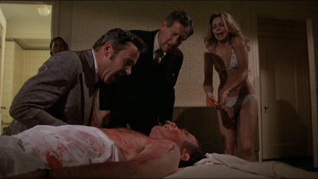 Harry Stoner beugt sich über einen leblos wirkenden Mann, im Hintergrund stehen Phil Greene und eine Prostituierte.
