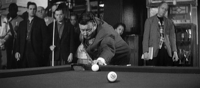 Jackie Gleason als Minnesota Fats beim Spiel; er steht an einer Ecke des Billardtisches und zielt auf die weiße Kugel, im Hintergrund beobachten Zuschauer interessiert den Spielzug.