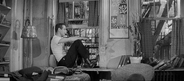 Felson sitzt im weißen Unterhemd leger auf der Fensterbank eines chaotischen Appartements.