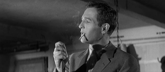 Paul Newman als Eddie Felson, der mit einer rauchenden Zigarette im Mund sein Queue spitzt.