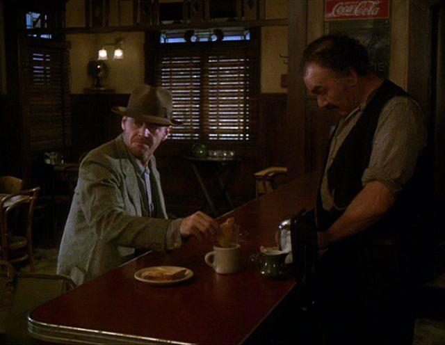 Frank Chambers sitzt an der Bar, hinter der Nick Papadakis arbeitet.