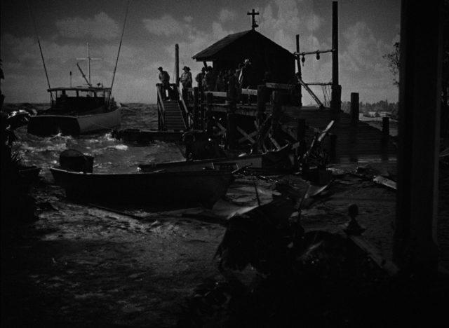 Blick auf den in Dunkel getauchten Bootssteg, an dem eine Gruppe Menschen steht und ein Boot im Wasser wankt.
