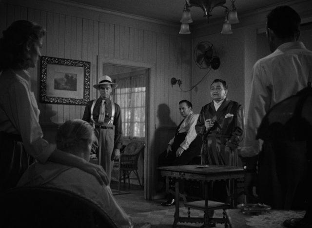 Gangster und Geiseln in einem Hotelzimmer, in der Mitte Johnny Rocco im Bademantel.