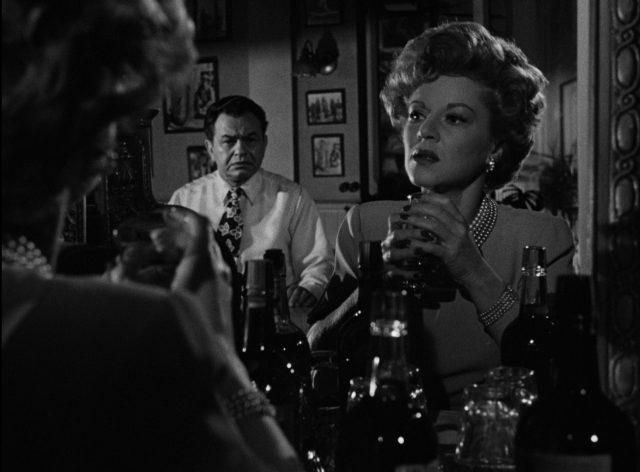 Gaye Dawn vor dem Spiegel der Bar, in dem Johnny Rocco mit finsterem Gesicht zu erkennen ist.