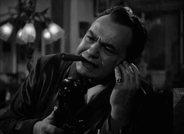 Nahaufnahme von Johnny Rocco beim Telefonat mit konzentriertem Gesicht: Im Mund prangt eine dicke Zigarre, an seiner Hand ein pompöser Ring.