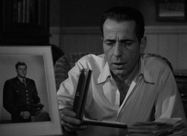 Nahaufnahme von Frank McCloud am Schreibtisch des Hoteliers, im Vordergrund ein Porträtbild des verstorbenen Kameraden respektive Sohnes.