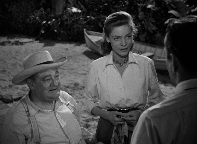 James Temple im Rollstuhl und neben ihm stehend Nora, beide im Gespräch mit McCloud, welcher der Kamera mit dem Rücken zugewandt ist.