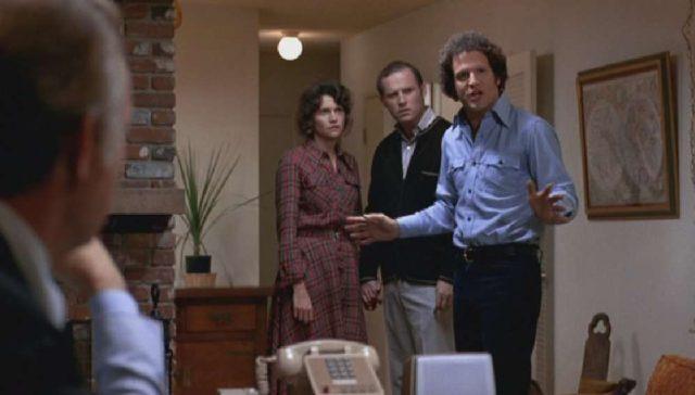 Brooks im Wohnzimmer mit den Yeager-Eltern, mit einer bestimmenden Geste.