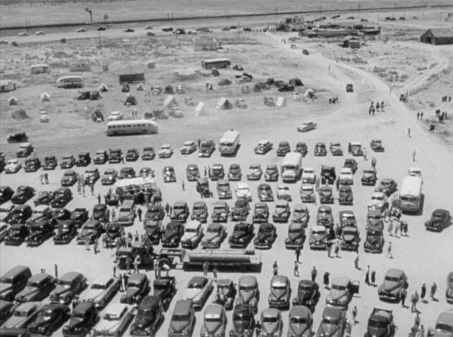 Blick von oben auf mehrere Reihen dicht geparkter Fahrzeuge in der Wüste von New Mexico.