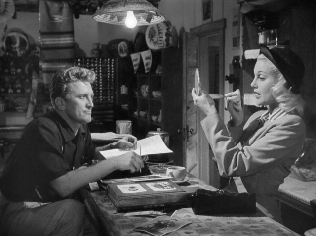 Chuck Tatum mit Schreibutensilien an der Imbisstheke, hinter der sich Lorraine Minosa schminkt.
